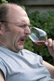 Disgust. Man pulling up his nose in disgust while smelling a glass of wine Royalty Free Stock Image