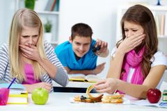 Disgust. Two disgusted girls looking at spider in one of their sandwiches Royalty Free Stock Photo