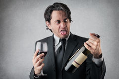 Disgusted businessman with a glass of wine stock photos
