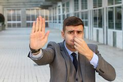 Disgusted businessman smelling something gross.  royalty free stock image