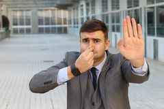 Disgusted businessman smelling something gross.  royalty free stock photography