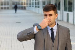 Disgusted businessman smelling something gross.  stock photography