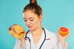Disgusted dietitian with sweet bun and grapefruit. Stock Image