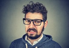 Disgusted male feels aversion towards something. Disgusted man feels aversion towards something, frowns face, on wall background. Emotional young adult royalty free stock photography