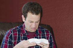 Disgusted man with a cold looking at his tissue after blowing his nose. Royalty Free Stock Image