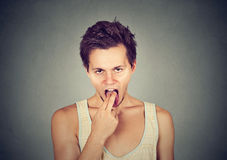 Disgusted man with finger in mouth displeased ready to throw up. On gray background. Human face expression, emotion Royalty Free Stock Photo