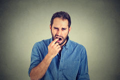 Disgusted man with finger in mouth displeased with situation ready to throw up Stock Images