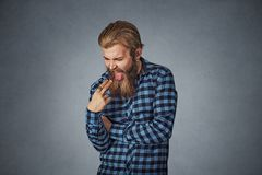 Disgusted man with finger in mouth displeased wants to throw up royalty free stock images