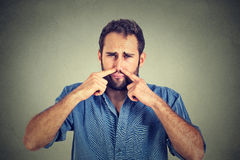 Disgusted man pinches nose with fingers hands looks with disgust something stinks. Portrait of disgusted man pinches nose with fingers hands looks with disgust royalty free stock photo