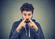 Disgusted man pinches nose with fingers looks with disgust. Something stinks bad smell situation isolated on wall background. Human face expression reaction Royalty Free Stock Photos