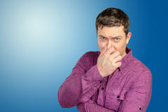 Disgusted man pinches nose with fingers Stock Photos