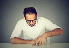 Disgusted man reading a text message scrolling down an email. Disgusted man reading a text message on mobile phone Royalty Free Stock Photography