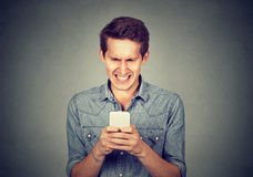Disgusted man reading a text message Stock Photography