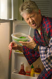 Disgusted Man Smelling Spoiled Rotten Food Royalty Free Stock Photography