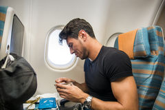Disgusted man tasting insipid food in plane. Young man feeling disgusted after tasting insipid food in the airplane. Horizontal indoors shot stock photos
