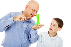 Disgusted by Science. Science teacher showing a plasma-like substance to a student. The boy is completely disgusted. Isolated on white royalty free stock photography