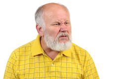 Disgusted senior bald man. Disgusted displeased senior bald man in yellow shirt Royalty Free Stock Photo