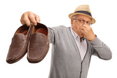 Disgusted senior holding stinky shoes. Disgusted senior holding a pair of stinky shoes isolated on white background stock photos