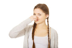Disgusted teen woman pinching nose. Stock Image