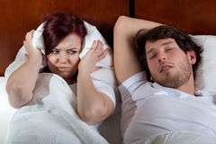 Disgusted wife and sleeping husband Stock Image