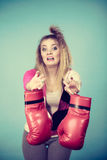 Disgusted woman holding boxing glove Royalty Free Stock Photos