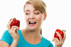 Disgusted woman holding in hand old wrinkled and fresh peppers, white background Royalty Free Stock Image