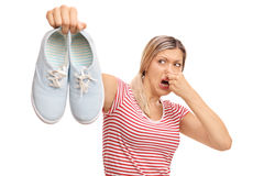 Disgusted woman holding stinky shoes Royalty Free Stock Image
