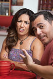 Disgusted Woman with Man in Cafe. Disgusted Hispanic women in cafe with man royalty free stock image