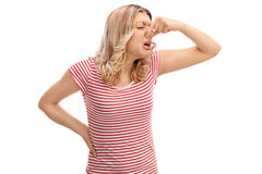Disgusted woman smelling something bad. Disgusted woman closing her nose and smelling something bad isolated on white background royalty free stock images