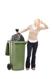 Disgusted woman standing next to a trash can. Full length portrait of a disgusted woman standing next to a trash can isolated on white background stock photography