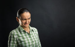 Disgusted woman. Standing over black background royalty free stock photo