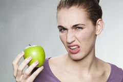 Disgusted woman unhappy with her apple Royalty Free Stock Photography