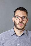 Disgusted young bearded businessman with eyeglasses expressing amazement and fear Royalty Free Stock Images