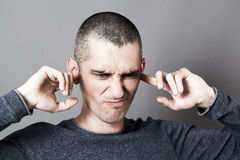 Disgusted young man plugging ears to refuse to listen Stock Images