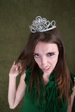 Disgusted Young Woman. Caucasian woman with tiara plays with her hair Stock Image