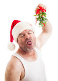 Disgusting Guy with Christmas Mistletoe. Unshaven middle-aged man in his undershirt, wearing a santa hat and holding mistletoe, waiting for a sloppy wet kiss royalty free stock photography