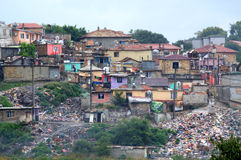 Disgusting illegal dump eyesore in slum. Illegal huts, shacks and  dump-tones of discarded junk around homes in the gypsy ghetto Maksuda,Varna,Bulgaria.Terrible Royalty Free Stock Photos