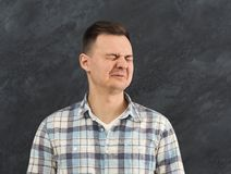 Young man expressing disgust at studio background. This is disgusting. Portrait of young man expressing negativity, feeling bad smell and grimacing, eating sour stock images