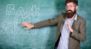 Disgusting school. Teacher dislike schooling. Teacher or educator stands near chalkboard with inscription back to school. Teacher unhappy disgusting face. Man stock images