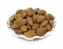 Dish of almond nuts. A small dish filled with all natural almond nuts on a white background Stock Images