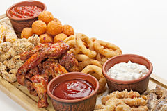 Dish of appetizers to beer. BBQ wings, fried squid rings,  grill Stock Image