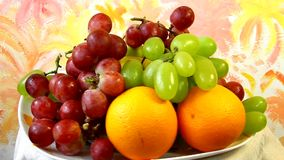 Dish with apples, grapes and oranges Stock Images