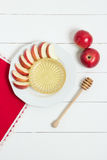 Dish with apples, honey and a spoon for honey on white wooden background. Jewish New Year, Rosh Hashanah, top wiev Royalty Free Stock Images