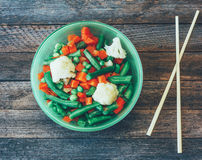 Dish Asian cuisine mixed vegetables and chopsticks on the old wooden table Royalty Free Stock Photography