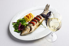 Dish with the baked fish and wine Stock Photos