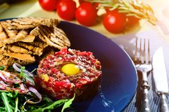Dish with beef tartare, tomatoes and leaves in cafe Royalty Free Stock Images