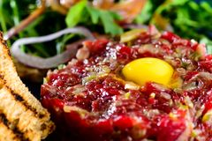 Dish with beef tartare, tomatoes and leaves in a cafe Royalty Free Stock Images