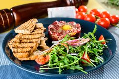 Dish with beef tartare, tomatoes and leaves in restaurant Royalty Free Stock Image
