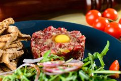Dish with beef tartare, tomatoes and leaves in a restaurant, clo Royalty Free Stock Image