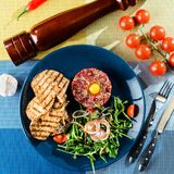 Dish with beef tartare, tomatoes and leaves on the table with kn Stock Photo